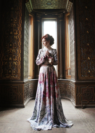victorian lady: young beautiful woman in pink dress posing in luxury palace