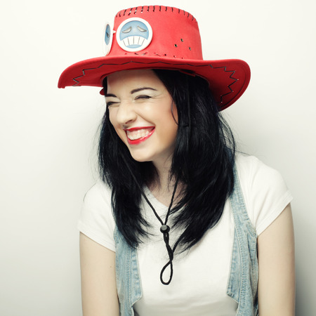 Portrait of Trendy Hipster Girl in Red Hat, studio shot photo
