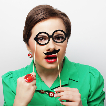 Attractive playful young woman holding mustache and glasses on a stick. Ready for party. photo