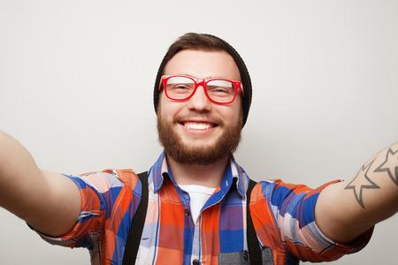 Tehnology concept: Gelukkig Selfie. Knappe jonge man met de camera en het maken van Selfie en glimlachend.