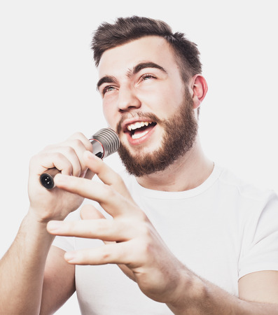 Life style concept: a young man with a beard wearing a white shirt holding a microphone and singing.Isolated on white. Special Fashionable toning photos.