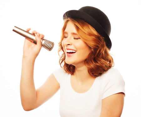 girl party: Happy singing girl. Beauty woman wearing white t-shirt and black hat with microphone over white background. Hipster style.