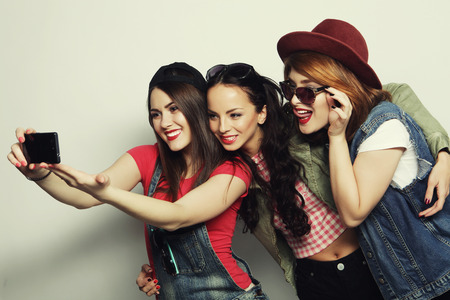 stylish couple: Three stylish sexy hipster girls best friends taking selfie with mobile phone Stock Photo