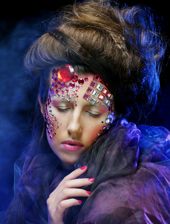 Beautiful woman with bright creative make up in blue smoke photo
