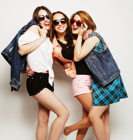 Fashion portrait of three stylish sexy hipster girls best friends, over gray background. Happy time for fun. Banque d'images