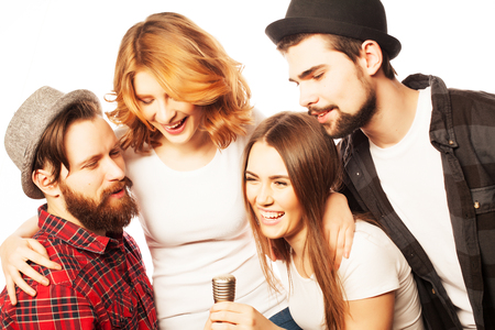 People, friendship  and leisure concept: group of young happy friends  having fun at karaoke, hipster style.Isolated on white. Stock Photo