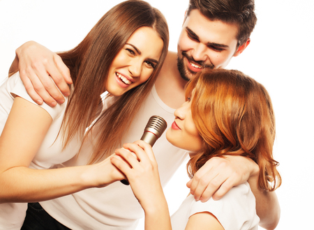 People, friendship  and leisure concept: group of young happy friends  having fun at karaoke, hipster style.Isolated on white. photo
