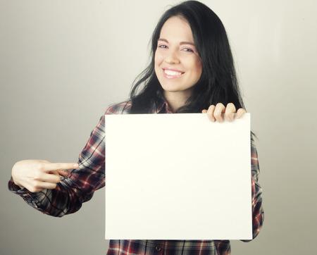 hoja en blanco: casual joven mujer feliz celebración de firmar en blanco Foto de archivo