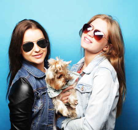 two happy teenage sisters with Yorkshire Terrier photo