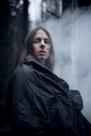 dark elf: young man with long hair in the dark forest
