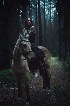 dark elf: Young man with long hair with horse in dark forest.