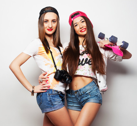 skaters: Two girl skaters go crazy and have fun together. Beautiful sporty women, positive emotion. Grey background.