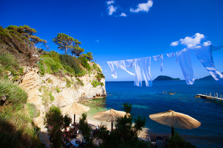 lounges: Row of Straw umbrellas and lounges at beach Zakynthos, Greece. Stock Photo