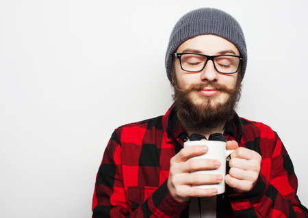 loony: Food, happiness and people concept: young bearded man with a cup of coffee against grey