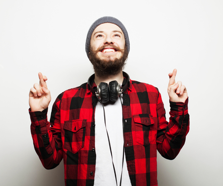 finger crossed: Life style and people concept:Waiting for special moment. Portrait of young bearded man in shirt keeping fingers while standing against white . Hipster style and positive emotions. Stock Photo