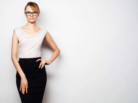smiling teenagers: Business, finance and people concept:  young  business woman wearing glasses. Over grey background.