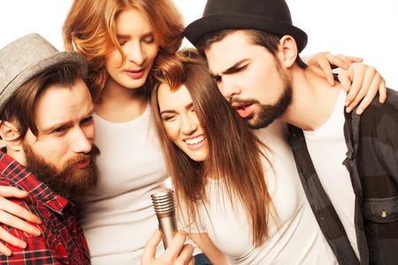 Mensen, vriendschap en vrije tijd concept: groep van jonge gelukkige vrienden plezier op karaoke, hipster style.Isolated op wit.