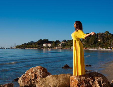 Fashion concept - Woman with long yellow dress walking alone on the beach photo