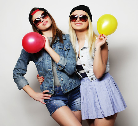 Two happy hipster girls smiling and holding colored balloons over white background Banco de Imagens