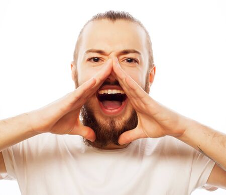 news background: life style and people concept: Good news! Young bearded man holding hand near mouth and shouting while standing against white background.