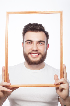 funny picture: Funny picture. Young man wearing beard holding picture frame in front of his face and fun hamming, isolated on white.