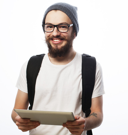 internet explorer: people, travel, tourism and technology concept - happy young bearded man in eyeglasses with backpack and  tablet  over white  background. Hipster style. Positive emotions.