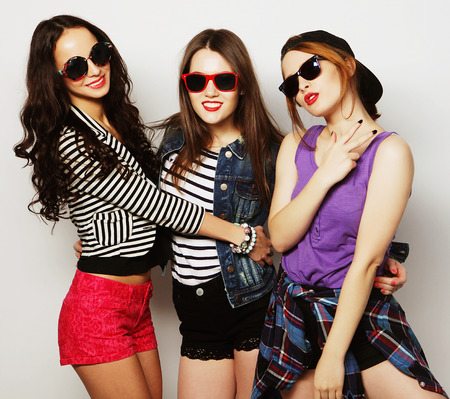 Three stylish sexy hipster girls best friends.Standing together and having fun. Looking at camera. Over gray background. Stock Photo