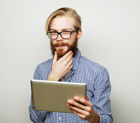 tehnology: Tehnology, education and lifestyle concept: young man  using a tablet computer - over gray background Stock Photo