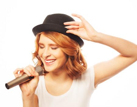 Gelukkig zingende meisje. Schoonheid vrouw met wit t-shirt en zwarte hoed met microfoon op witte achtergrond. Hipster stijl.