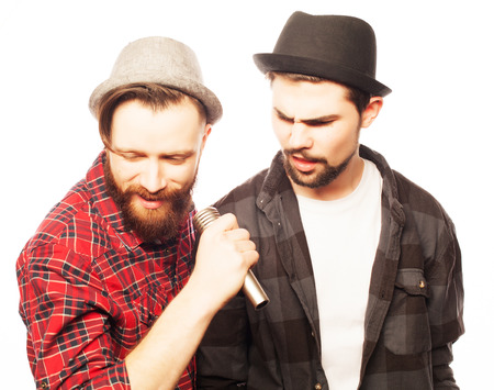 singing: Hipsters: two young mens singing with microphone. Isolated on white. Stock Photo