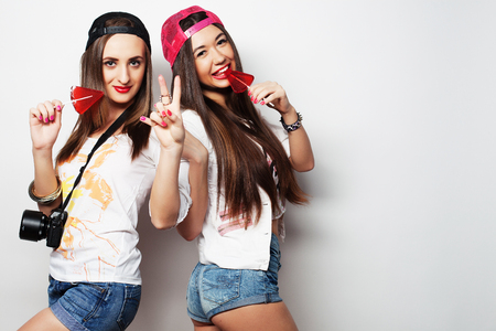 babes: Fashion portrait of two young pretty hipster girls wearing bright make up and holding candys. Studio portrait of two cheerful best friends sisters having fun and making funny faces. Stock Photo
