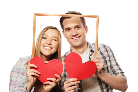 lovely couple: lovely couple holding frame and red hearts  over white background.