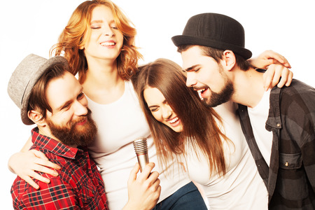 People, friendship  and leisure concept: group of young happy friends  having fun at karaoke, hipster style.Isolated on white. Standard-Bild