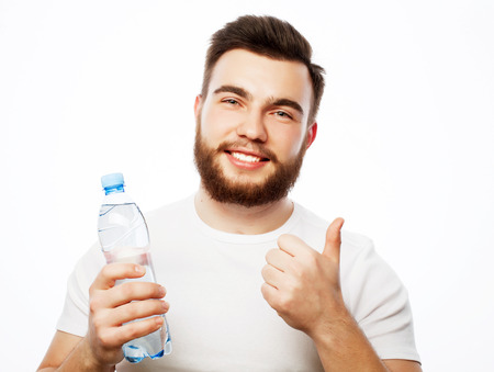 Fitness, sport  and lifestyle concept: smiling muscular sportive man wearing white shirt with bottle of water. Isolated on white. photo