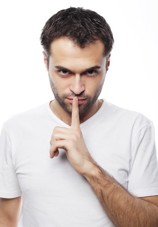 shhh: life style  and people concept: young man wearing white t-shirt making silence gesture, shhhhh!!