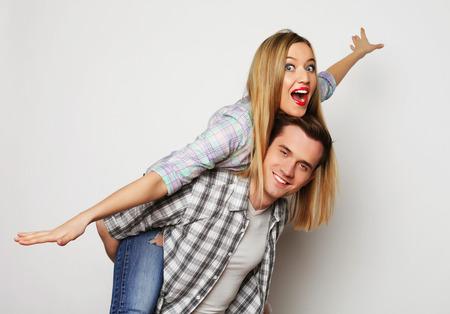 couple  amoureux: amour, la famille et les gens notion: joli couple, jeune homme portant copine sur le dos.