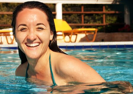 25 30 years: Portrait of a young woman smiling in a swimming pool