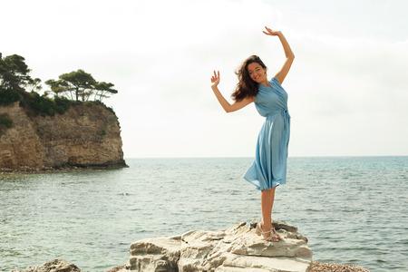 maxi dress: Young happy woman posing near sea, summer vacation