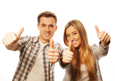 two thumbs up: people, friendship, love and leisure concept - lovely couple with thumbs-up gesture isolated on white