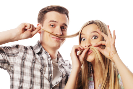 making love: people, friendship, love and leisure concept - beautiful young loving couple making fake moustache from hair while standing isolated on white.