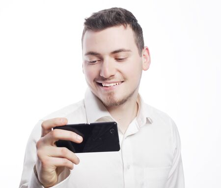 tehnology: business,tehnology and people concept - Handsome happy business man reading an SMS on smartphone against white background