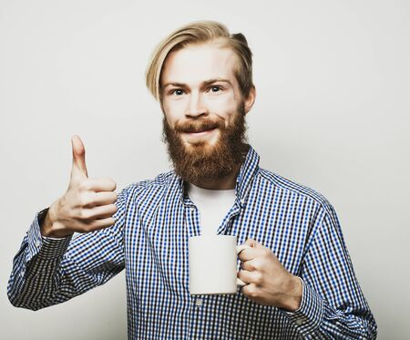 okey: life style, happiness and people concept: young bearded man with a cup of coffee in hand and showing okey, against grey background. Stock Photo