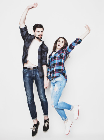 life style, happiness and people concept: Happy loving couple. Jumping over light grey background. Special Fashionable toning. 写真素材