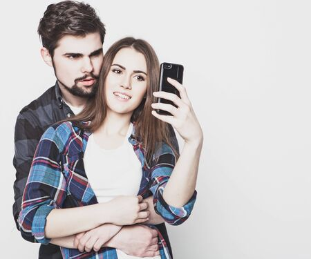 couple in love: tehnology, internet, emotional  and people concept: Capturing happy moments together. Happy young loving couple making selfie and smiling while standing against white background. Stock Photo