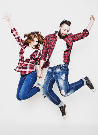 life style, happiness and people concept: Happy loving couple. Jumping over light grey background. Special Fashionable toning. Standard-Bild