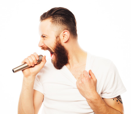 mike: Life style concept: a young man with a beard wearing a white shirt holding a microphone and singing.Isolated on white.