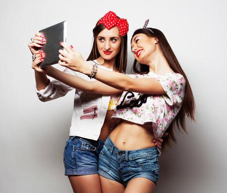 friendliness: Dos mujeres muy jóvenes vistiendo ropa de verano y que toman un autorretrato con una tableta  estudio sobre fondo gris.