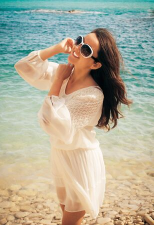 yearning: Happy woman in summer white dress on beach. Caucasian girl relaxing and enjoying peace on vacation.