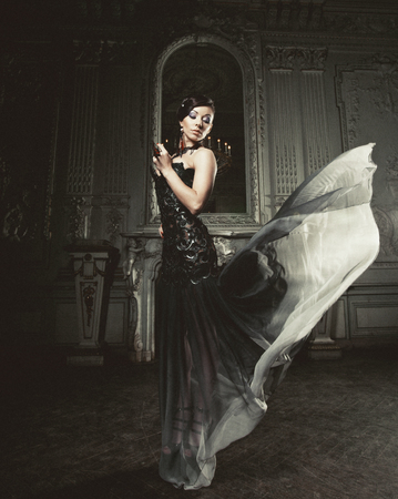 young elegance woman with flying dress in room photo