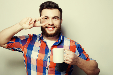 cute guy: food, happiness and people concept: young bearded man with a cup of coffee against grey background
